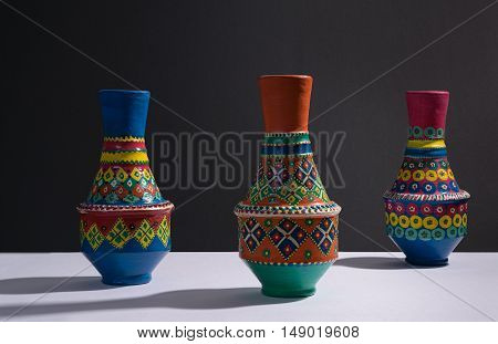 Still life of three artistic painted colorful handcrafted pottery vases with harsh shadow on white table and black wall