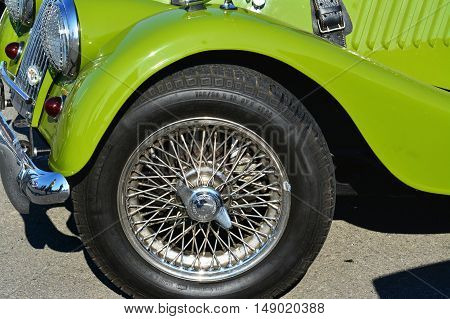 CLUJ-NAPOCA ROMANIA - SEPTEMBER 24 2016: Wire-spoked wheel of a vintage Morgan Plus 4 roadster classic car parked in the parking lot.