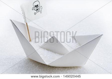 White sugar in a paper boat in a sugar sea