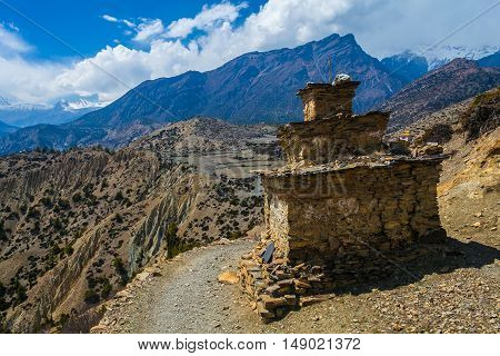 Tibetan prayer stupa or prayers place of the faithful Buddhists in center Mountains Path. Blue Sky Background. Horizontal photo