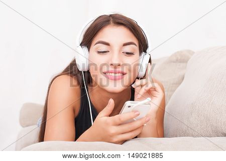 Young beautiful woman in headphones listening music and using her smartphone on couch in living room