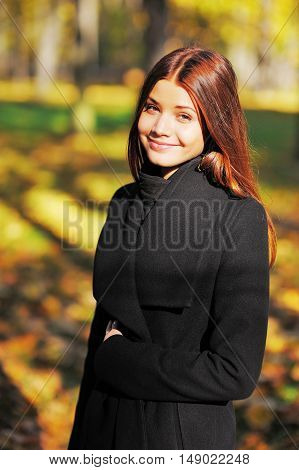 Cute smiling brown-eyed girl with long brown hair in a black coat autumn park.