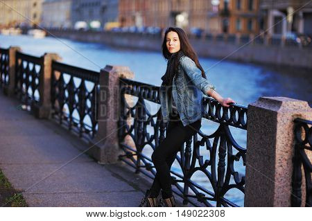 Young pretty brunette girl posing on the St. Petersburg waterfront in the rays of the setting sun on a blurred background of the river and the city's architecture.