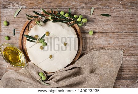 Top view of yeast dough for olive bread decorated with branch of olive tree and olive oil on a rustic wooden background.