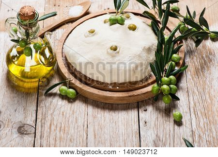 Freshly prepared bread dough with green olives and bottle of olive oil on a rustic wooden background.