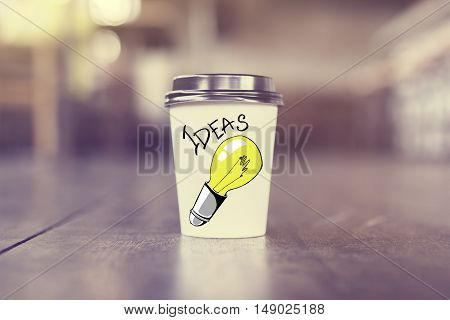 Take away coffee cup with creative light bulb sketch. Close up. Idea concept