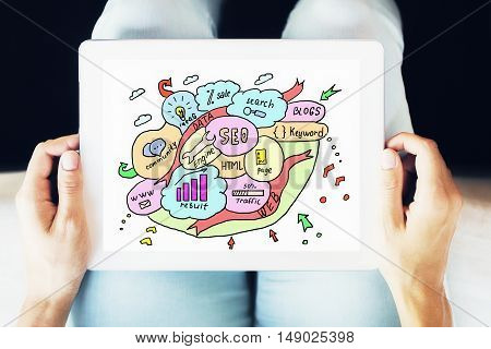 Female hands holding digital tablet with creative SEO sketch. Search engine optimization concept