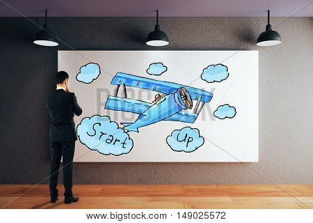 Thoughtful businessman in modern interior looking at whiteboard with creative small plane sketch. Start up concept. 3D Rendering