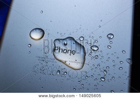 PARIS FRANCE - SEP 26 2016: New Apple iPhone 7 Plus unboxing and testing - iPhone engraved logo covered with rain drops. New iPhone7 is one of the best waterproof smart phone in the world