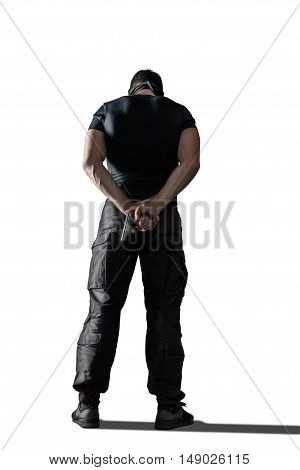 Standing man with gun wearing black military uniform isolated on white background, rear view