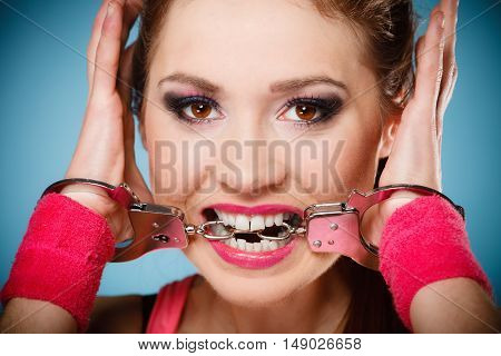 Teen crime arrest and jail - Criminal teenager girl prisoner woman in handcuffs blue background