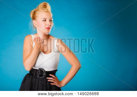 Retro pin up girl style. Young attractive woman sending hand kiss. Studio shot on blue background.