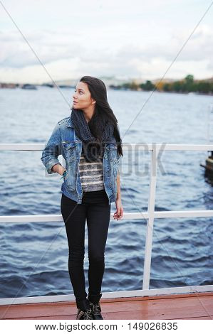 Slim beautiful brunette in jeans jacket and scarf stands on the pier and looking around the cool wind ruffled his hair. Back on blurred background can be seen the outlines of St. Petersburg.