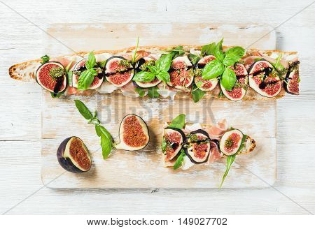 Long baguette sandwich with prosciutto meat, mozzarella cheese, arugula, figs and basil on shabby white painted wooden board over white background. Top view, horizontal composition