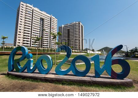 Rio de Janeiro, Brazil - September 12, 2016: Rio 2016 sign at the Olympic and Paralympic village with athletes residences in background.