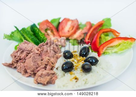 rice tuna chopped vegetables and olives in a white plate on a white background