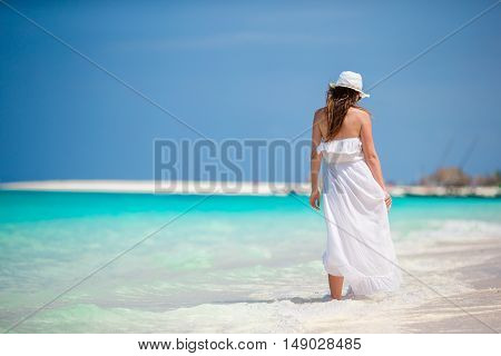 Young beautiful woman during tropical beach vacation. Enjoy suumer vacation alone on the beach at Africa with frangipani flowers in her hair