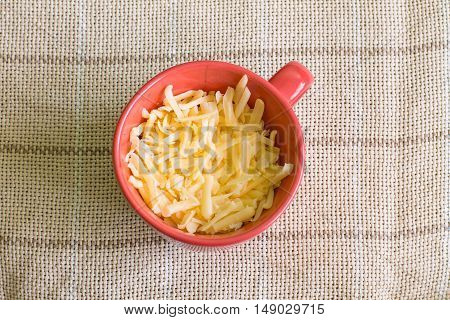 Grated Gouda cheese in red cup on linen tablecloth. Aerial view