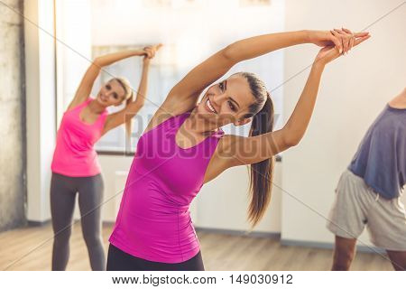 Beautiful sports people are stretching and smiling while doing yoga in modern fitness hall