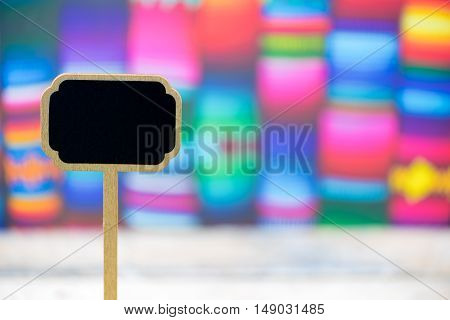 Wooden Mini Blackboard Label Over Colorful Traditional Mexican Blankets Background