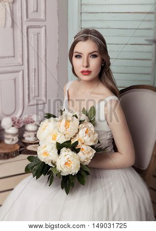 Beautiful young bride with flowers romantic decoration pink and green. Wooden boxes bottles and different wedding decoration