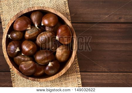 Chestnuts in wooden bowl photographed overhead on wood with natural light (Selective Focus Focus on the chestnuts on the top)