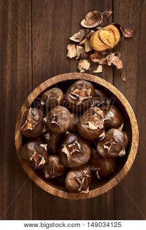 Freshly roasted or baked chestnuts in wooden bowl photographed overhead with natural light (Selective Focus Focus on the chestnuts on the top)