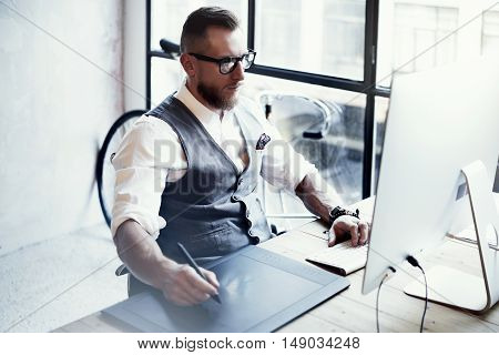 Bearded Graphic Designer Working Digital Tablet Drawing Desktop Computer Wood Table.Stylish Young Man Wearing Glasses White Shirt Waistcoat Work Modern Loft Creative Startup Project.Blurred Horizontal