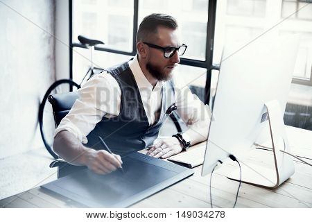 Bearded Creative Designer Working Drawing Digital Tablet Desktop Computer Wood Table.Stylish Young Man Wearing Glasses White Shirt Waistcoat Work Modern Loft Online Startup Project Blurred