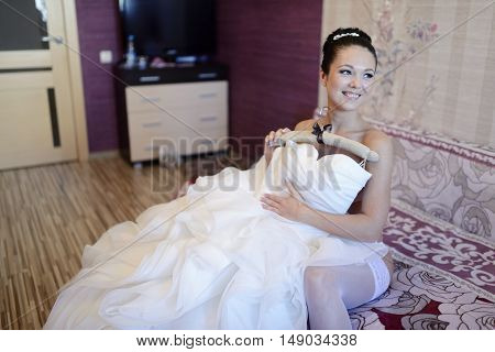 Beautiful bride in lingerie is watching a wedding dress. Beauty model girl in white clothes. Female portrait with bridal gown for marriage. Woman with curly hair and lace veil. Cute lady indoors