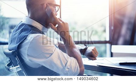 Closeup Bearded Businessman Wearing White Shirt Waistcoat Working Modern Loft Startup Computer.Creative Young Man Using Mobile Phone Call Partner Meeting.Gentleman Guy Looking Watch Workplace.Blurred