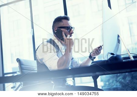 Bearded Businessman Analyzes Business Strategy Modern Workplace.Young Man Working Startup Desktop.Using Smartphone Making Consult Stock Trader.Guy Work Office Wearing White Shirt Waistcoat.Blurred