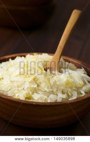 Sauerkraut in wooden bowl photographed with natural light (Selective Focus Focus one third into the sauerkraut)