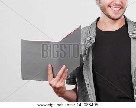 Leisure education literature concept. Young handsome male student holding textbooks book