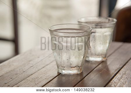 Glass water on wooden table with poor light background.
