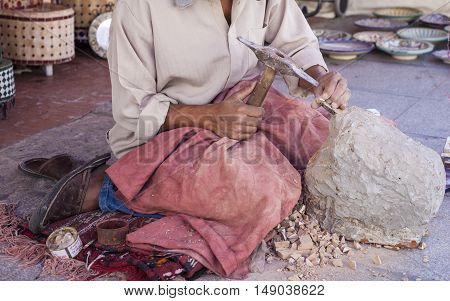 Artisan makes pieces for mosaic craftwork. He is shaping pieces from glazed tiles