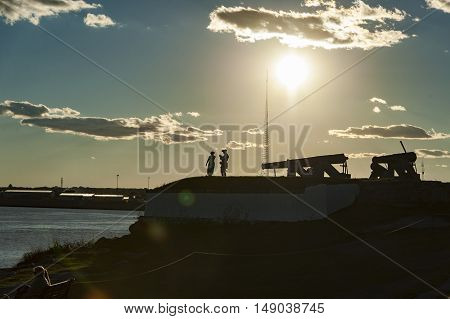 Fairhaven Massachusetts USA - September 24 2016: Members of Fairhaven Village Militia silhouetted by late afternoon sun while preparing for firing of cannon at Fort Phoenix in Fairhaven Massachusetts in a Revolutionary War reenactment