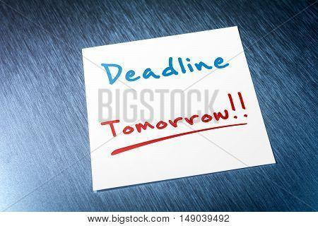 Deadline Sticky Note For Tomorrow On Paper On Brushed Aluminum Of Fridge