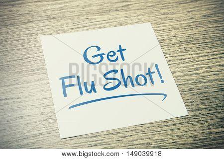 Get Flu Shot Reminder On Paper On Wooden Table