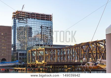 South Boston Massachusetts USA - August 25 2016: Sunrise lights construction at One Seaport Square in South Boston and the Northern Avenue Bridge on Fort Point Channel