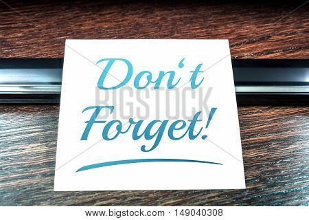 Don't Forget Reminder On Paper Lying On Wooden Table