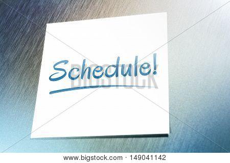 Schedule Reminder On Paper Lying On Brushed Aluminum Of Fridge