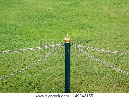 Metal chain fence for protection to the meadow in the city park.