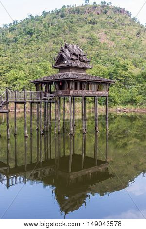 Old teak church in the small lake which in front of the mountain.