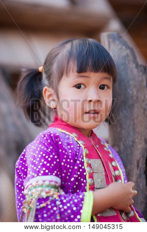 CHIANGMAI,THAILAND - JANUARY 11, 2015: Unidentified Palaung kid in the Palaung traditional costume poses for the camera. Palaung people is a minority ethnic group living in northern Thailand