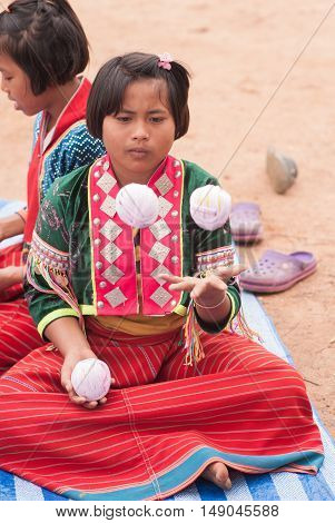 CHIANGMAI,THAILAND - JANUARY 11, 2015: Unidentified Palaung kids in the Palaung traditional costume are juggling with balls. Palaung people is a minority ethnic group living in northern Thailand