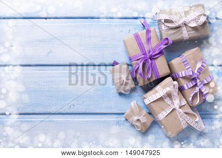 Different festive gift boxes with presents on blue wooden background. Selective focus. Place for text.