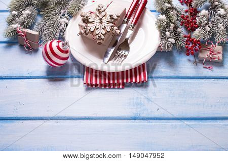 White plate knife and fork napkin and christmas decorations in white and red colors on blue wooden table. Selective focus. Place for text.