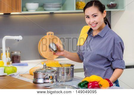 Young beautiful happy asian female preparing food