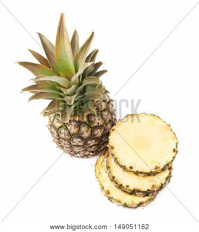 Whole raw fresh pineapple with stack of slices isolated over white background